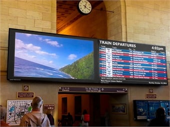 An LCD sign by Daktronics displays departure information alongside desirable imagery at New Haven, Conn.'s Union Station.