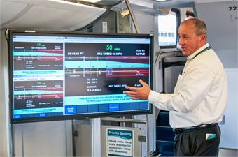 Neil Brown, manager, onboard PTC systems, Metrolink, explains to attendees at the revenue service event in March how positive train control works.