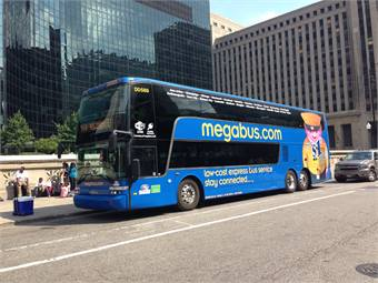 A Megabus double decker bound for Milwaukee waits on Canal Street outside of Chicago Union Station. The fare for this popular afternoon departure undercuts Amtrak by a significant margin (Xhoana Ahmeti).