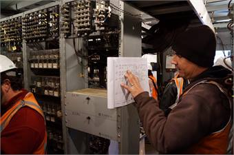 Metro-North Signal Department workers consult circuit diagrams, make signal changes and test the system at Spuyten Duyvil. Photo: Metropolitan Transportation Authority / J. P. Chan.