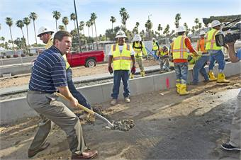 Phoenix Mayor Greg Stanton assists with placement of the first track on Valley Metro's Northwest Light Rail Extension.
