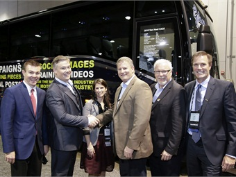 John Benjamin celebrates the purchase of a new Van Hool CX35 with Christian Riddell and others, including ABC's Roman Cornell (far left).