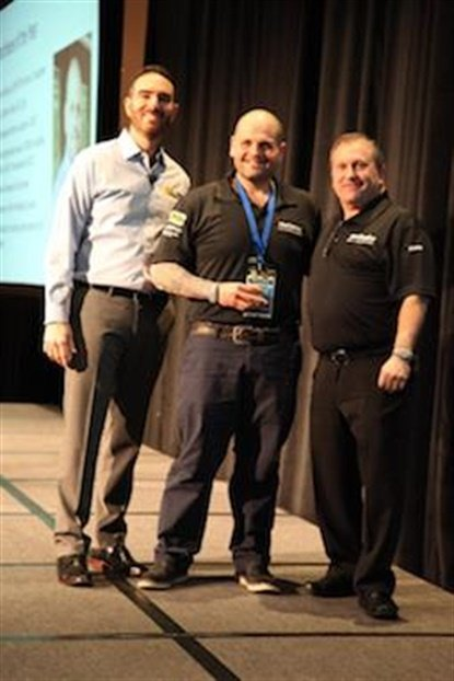Joe Cooper, center, accepts the Franchisee of the Year Award from Meineke'sDanny Rivera and Rob Fillman.