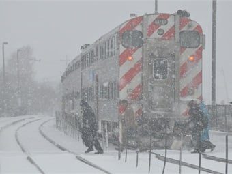 Commuters crossing in the middle of a storm. Photo: Metra/Mark Llanuza