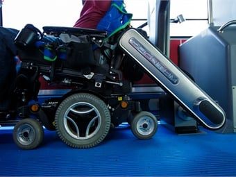 """How it works: With the vehicle safely stopped, the passenger centers their wheelchair or scooter against the backrest and presses a button to engage the automatic locking sequence. Next, the Quantum's """"arms"""" move to secure the wheelchair in place, all in under 25 seconds, without requiring the drivers' assistance. Meanwhile, the securement arms continually adjust their grip as needed throughout the journey. Then, once the vehicle stops at a destination, the Quantum's release sequence can be engaged so the passenger can disembark."""