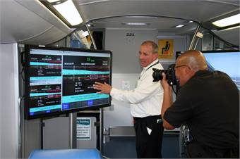 Metrolink's Neil Brown, manager of the agency's on-board PTC systems, explains PTC technology to a newspaper photographer on Feb. 20, 2014 at Los Angeles Union Station.