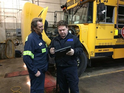 One mechanic gave new inspectors a more complete picture of the myriad responsibilities and ever-fluctuating and unpredictable nature of a school bus mechanic's job in an open letter. Shown here is a Michigan State Police inspector, right, working with a mechanic in 2016.