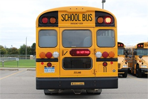 Ten districts across Michigan have been testing Driver Alert Lighting System, a sign placed in the middle of the back door, to see if it reduces vehicle pass-bys. Shown here is a Zeeland Public Schools bus equipped with the system.