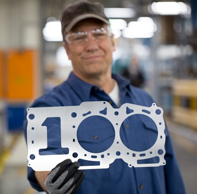 In honor of Fel-Pro's 100th anniversary, the Fel-Pro team designed a special head gasket as a symbol of the firm's milestone. TV celebrity and working-man's spokesman Mike Rowe holds a laser-cut core for the special MLS gasket.