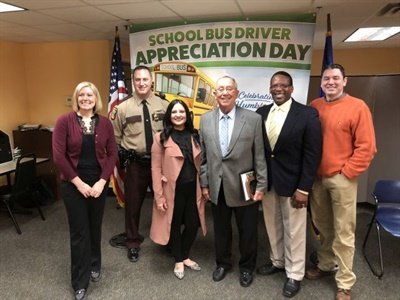 School bus driverBill Drigans (center) was honored for helping to prevent a child from being struck by a stop-arm runner at a press conference for Minnesota's School Bus Driver Appreciation Day.
