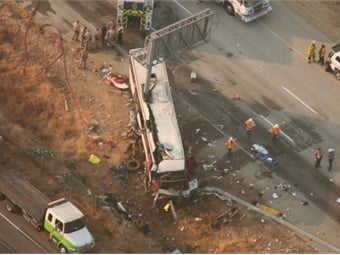 Aerial view of SR-99 northbound lanes, showing motorcoach at final rest and impact damage caused by 14-inch-diameter signpost penetrating two-thirds of vehicle, from front to back. (Photo: California Highway Patrol)