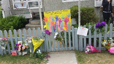 Students paid tribute to Phemie by bringing flowers and cards and decorating the fence in front of her step where she had always sat to wave to the kids and held a sign with a special message for that day.