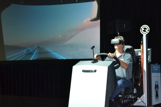 A driver wearing virtual reality goggles in a truck simulator demonstrates such technologies as adaptive cruise control, lane departure warnings, and active brake assist.