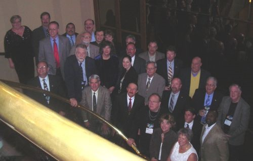 Current state directors and NASDPTS board members Diana Hollander (left) and Max Christensen (near left, with red tie) are seen here with more than two dozen now-former state directors at the 2006 NASDPTS conference. In the bottom row (near center, in dark suit) is Charlie Hood, then the Florida state director and now executive director of NASDPTS. Photo courtesy Derek Graham, former North Carolina state director