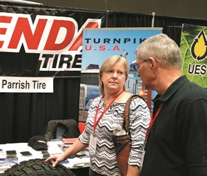 Mike and Dana Kelly of North Elkin Tire & Automotive in Elkin, N.C., check out a Kenda tire at the Parrish Tire Co. booth during the NCTDA Trade Show.
