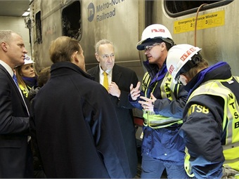 NTSB investigators brief Members of Congress while touring facility where train is being examined. NTSB