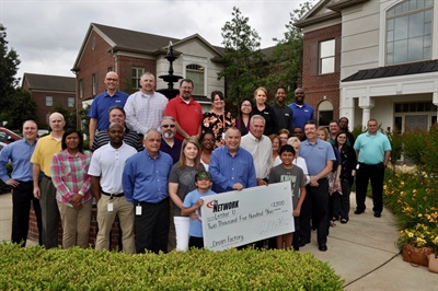 Network President David Prater and the Dream Factory's Brian Jeungling (bothfront row, right)present Lester U. and his family with a $2,500check that helped fund the11-year-old's dream trip to Disney World.