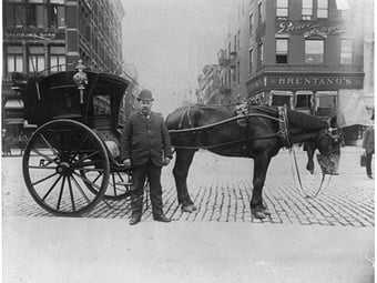 An 1896 photo of a New York City hansom driver standing in front of horse and cab.