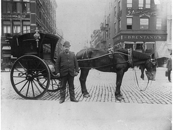 An 1896 photo of a New York City hansom driver standing in front of horse and cab. Public Domain