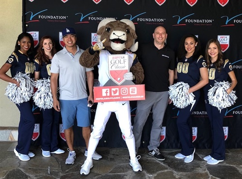 Nexen's senior director of marketing Kyle Roberts (right of mascot) poses with the Los Angeles Rams mascot and cheerleaders after a round of golf to help raise money for cancer research.