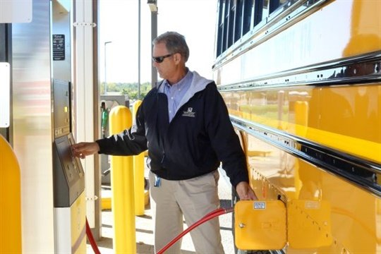 David Curry, lead trainer at North Kansas City Schools, refuels one of the district's 124 new CNG buses at a fast-fill station.