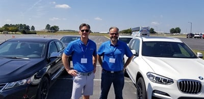 Sailun Tire Americas' Brian Mielko, vice president of sales, and Mark Pereira, marketing communications manager, stand between the test vehicles during their company's event in Atlanta.