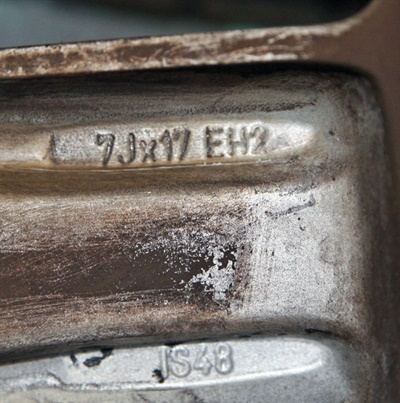 """On this Mini Cooper wheel, """"EH2"""" at the end of the size spec means the wheel is designed for run-flat tires. The """"IS48"""" below the size indicates offset."""