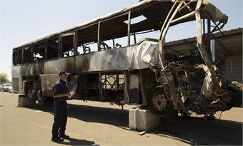 Robert Accetta documents the damaged motorcoach. Courtesy NTSB