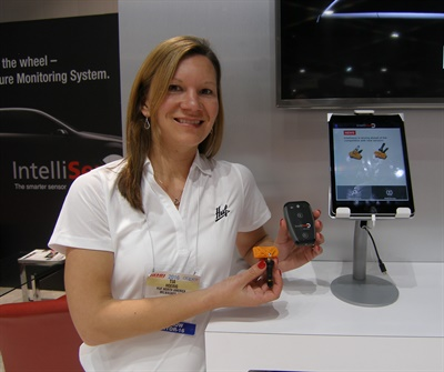 Tia Hoerig, program management analyst for Huf North America, holds the HC1000 wireless adapter, which enables the TPMS sensor and mobile device to communicate.
