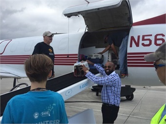 Palm Tran Executive Director Clinton B. Forbes assists in loading pets on an aircraft at Palm Beach International Airport following Hurricane Irma on Sept. 13.