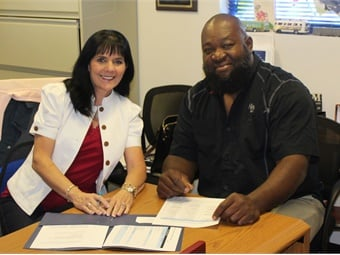Palm Tran Organizational Development Manager Liliane Finke, Ed.D smiles alongside Maintenance Technician Christopher Love who utilized the Upward Mobility program to successfully progress in his career.