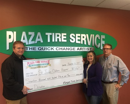 Mark Rhodes, left, and Scott Rhodes present Plaza Tire Service's donation to Jenny Pagel-Guile of St. Jude Children's Research Hospital.