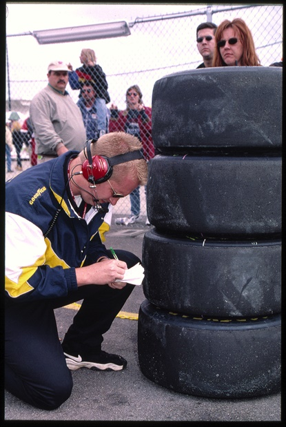 In this undated photo from Goodyear, a tire engineer checks a stack of tires for a NASCAR race.