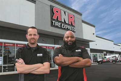 Matt King (left, pictured with Reggie Goodwin, manager of the 100th store) started with RNR as a tire technician. He is now a regional manager.