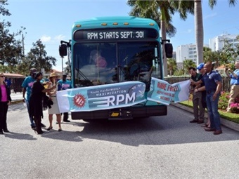For the special ribbon-cutting ceremony, a bus instead of scissors cut through a banner held by Palm Tran staff, Palm Tran Service Board (PTSB) members and local county officials. Palm Tran