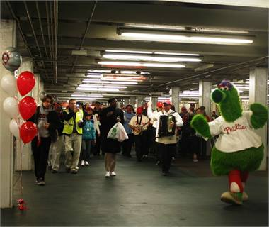 The Phillie Phanatic leading passengers to SEPTA's Phillies Express.