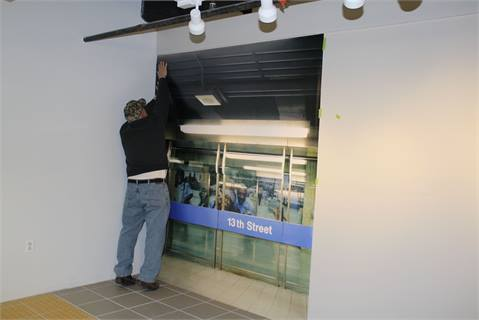 A worker installs a mural of SEPTA's 13th Street Market-Frankford Line Station.