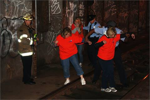"A SEPTA police officer, Philadelphia police officer and Philadelphia firefighter assist ""victims"" through the subway tunnel."