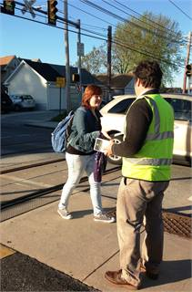 SEPTA Environmental Safety Officer Richard Harris hands safety information to a student heading to a school located near SEPTA's Leamy Avenue trolley station.