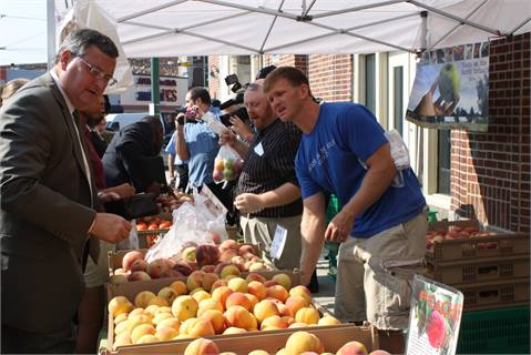 SEPTA GM Joseph Casey, shown left, and the elected officials made the market's first purchases of the day, buying apples and peaches.