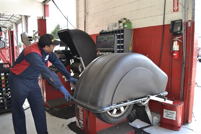 Joaquin Garcia balances a tire at Redwood General Tire Pros in Redwood City, Calif.