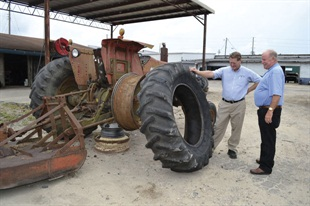 Freddy Norris, left, shows Ricky Benton a torn-up tractor tire owned by a customer who couldn't afford a new tire. So Norris sold him a used tire at minimal cost. Norris manages the original Black's Tire store in Whiteville, N.C., and is the first manager Benton ever hired.