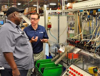 Rigney, right, talks with Robert Bradshear, valve core manufacturing supervisor.