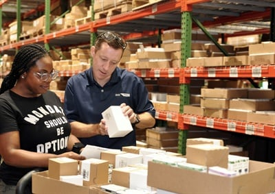 Kanisha Chavis, warehouse associate, receives hands-on help from Rigney.