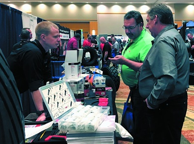 Bobby Hendry from 31 Inc. talks to Mike Fleming, equipment supply manager for Point S, and Marc Thompson from Point S Everett in Everett, Wash.