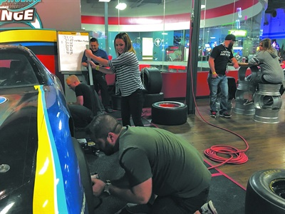 Tire Factory moved its dealer meeting out of Oregon and planned new activities for dealers, including a visit to Octane Raceway and a timed pit crew challenge. Tiffany Fox prepares to lower the jack once her teammates from Point S J&J Tire & Auto Service in Helena, Mont., finish their tire installations.