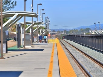 The Carlsbad Poinsettia Station improvements include new shelter enhancements, a pedestrian undercrossing, lengthened passenger platforms, fencing between tracks for added safety, and better customer amenities.