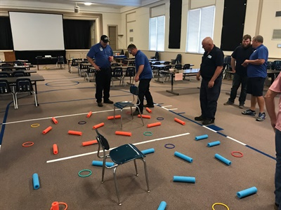 """Management class attendees took part in a leadership game called """"catching a snake"""" with the objective of the group, or """"snake"""" working together to fill a bucket with 10 balls. Photo courtesy Mike Vivar"""