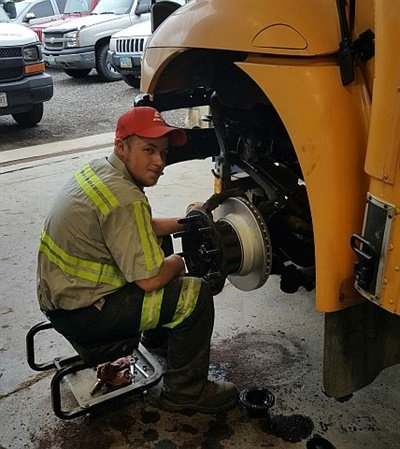 Prioritizing routine maintenance can prevent inspection violations. Austin Hamlin, a mechanic for school bus contractor VAT, performs routine brake service.