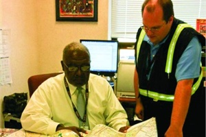 Arlington (Va.) Public Schools Director of Transportation Gregory Sutton (left) communicates with his drivers regularly to keep abreast of potential hazards on their routes. He's pictured with Justin Kirby, one of the operation's swing/lead bus drivers.